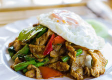 Stir fried pork with curry paste serve with fried egg Stock Photos