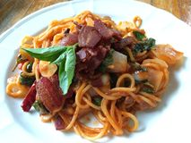 Stir-Fried Spaghetti and Crispy Bacon. Spicy minced salmon salad is fusion food Royalty Free Stock Images