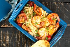 Stir-fried spaghetti with grilled shrimps and tomatoes - Italian fusion food style. royalty free stock images