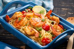 Stir-fried spaghetti with grilled shrimps and tomatoes - Italian fusion food style. Stir-fried spaghetti with grilled shrimps and tomatoes - Italian fusion food royalty free stock photos