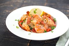 Stir-fried spaghetti with grilled shrimps and tomatoes - Italian fusion food style royalty free stock photo