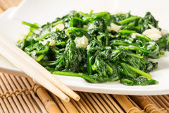 Stir fried spinach. Stir fried green spinach with chop sticks Royalty Free Stock Images
