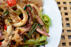 Stir-fried squid and basil on white plate and blur bamboo basket Stock Images