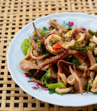 Stir-fried squid and basil on white plate and blur bamboo basket Royalty Free Stock Photo
