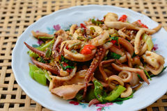 Stir-fried squid and basil on white plate and blur bamboo basket Stock Photo
