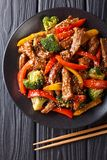 Stir-fried teriyaki beef with red and yellow bell pepper, broccoli and sesame seeds close-up on the table. Vertical top view. Stir-fried teriyaki beef with red royalty free stock image