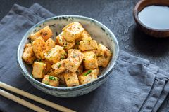 Stir Fried Tofu. In a bowl with sesame and greens. Homemade healthy vegan asian meal - fried tofu stock photography