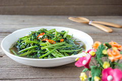 Stir Fried Water Spinach or pak boong fai daeng on white dish Royalty Free Stock Image