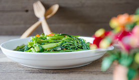 Stir Fried Water Spinach or pak boong fai daeng on white dish Stock Image