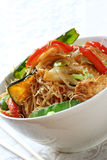 Stir-fry. Chicken, vegetable and noodle stir-fry, in white bowl with chopsticks Stock Photo