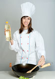 Stir fry. Young chef in a neutral background with a wok and a bottle of oil Royalty Free Stock Photo