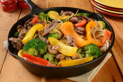 Stir fry. Beef stir fry in a cast iron skillet on a rustic wooden table Royalty Free Stock Photography