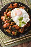 Stir-Fry Chicken with basil, green beans and a fried egg on a pl Stock Photography