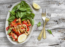 Stir fry of chicken breast and sweet red pepper and fresh spinach. On a light wooden background Stock Photography
