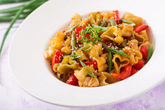 Stir Fry from chicken fillet, green beans and paprika with pasta Stock Photo