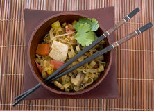 Stir Fry And Chopsticks. Stir Fry in a wooden bowl with chop sticks on a bamboo mat Stock Photography