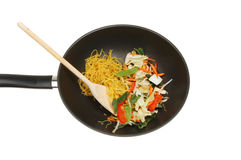 Stir fry. Ingredients with a wooden spoon in a wok isolated against white royalty free stock images