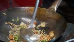 A stir fry meal being prepared in a hotel or restaurant kitchen flambe style.  stock footage
