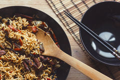 Stir fry noodles in a black pan with bamboo ladle, and with black shiny bowl Royalty Free Stock Photo