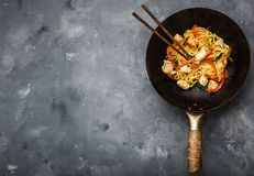 Stir fry noodles. In traditional Chinese wok, chopsticks, ingredients. Space for text. Asian noodles with vegetables, chicken. Wok noodles. Rustic stone stock images