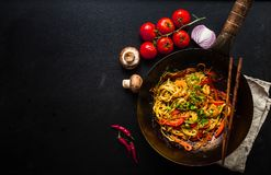 Stir fry noodles. In traditional Chinese wok, chopsticks, ingredients. Space for text. Asian noodles with vegetables, shrimps. Wok noodles. Black dark stock photography