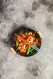 Stir fry with prawns, vegetables, soy sause and sesame. In the wok. Traditional asian food. Top view on grey stone background royalty free stock images