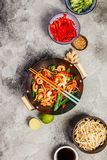 Stir fry with prawns, vegetables, soy sause and sesame. In the wok. Traditional asian food. Top view on grey stone background stock images