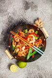 Stir fry with prawns, vegetables, soy sause and sesame. In the wok. Traditional asian food. Top view on grey stone background stock photo