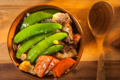 Stir-fry Snow Peas with Carrot with Shiitake and pork. On the wood table Royalty Free Stock Image