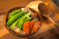 Stir-fry Snow Peas with Carrot with Shiitake and pork. On the wood table Royalty Free Stock Images