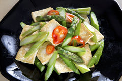 Stir-fry tofu and asparagus. Delicious stir-fry tofu and asparagus on dish Royalty Free Stock Photo