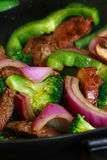 Stir fry in wok. Vertical picture of beef stir fry with onions, mushroom, green pepper,  and broccoli in a wok Stock Image