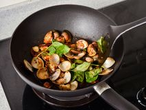 Stir-frying Ginger and clams at high heat to bring forth the savory aroma with sesame oil. In recipe Royalty Free Stock Image