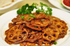 Stir-frying lotus root slices with sauces Stock Image
