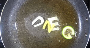 Stir-frying mixed alphabet letters, word Hunger stock footage