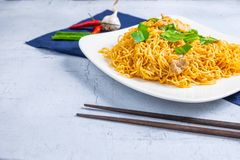 Stir noodles with vegetables in a white plate on a wooden floor stock photos