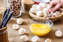 Stir a spoonful of raw eggs in a glass dish. A hand with a spoon is stirring raw eggs in a glass dish. Table with eggshell covered in burlap. Blurred background royalty free stock photo