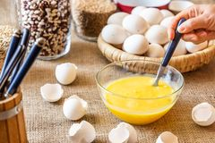 Stir a spoonful of raw eggs in a glass dish. A hand with a spoon is stirring raw eggs in a glass dish. Table with eggshell covered in burlap. Blurred background royalty free stock photos