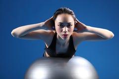 Stirata asiatica orientale della parte posteriore della donna sulla sfera di esercitazione Fotografia Stock Libera da Diritti