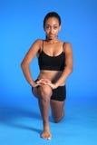 Stirata del flessore dell'anca di inginocchiamento dalla donna di colore di misura fotografia stock libera da diritti