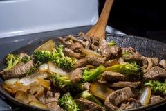Stirfry βράσιμο στον ατμό μπρόκολου και κρεμμυδιών βόειου κρέατος στο τηγάνι Στοκ Φωτογραφία