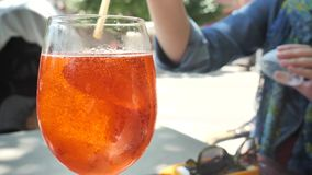 stiring切片在coctail的桔子的女孩喷在冷玻璃杯的aperol晴朗的温暖的天在街道咖啡馆 股票视频