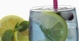 Stiring en un vidrio con la bebida fr?a, hojas de la menta, cal, lim?n, pasas, hielo metrajes