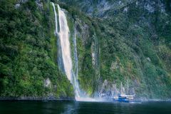 Stirling Falls at Milford Sound. A cruise boat is getting close to Stirling Falls at Milford Sound in Fiordland National Park, New Zealand, South Island Stock Photography