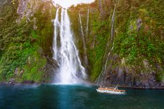 Stirling Falls at Milford Sound, New Zealand. Stirling Falls at Milford Sound in South Island of New Zealand. Tourist ferry approaching Stirling Falls, the Royalty Free Stock Image