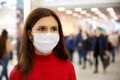 Stirnrunzeln und Blicke eines Besorgnis erregendes jungen Mädchens weg sie hat im Mall und ist vor Infektion Angst lizenzfreie stockfotos