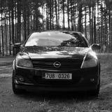 Stirrande Splavy, Tjeckien - Augusti 12, 2017: svart Opel Astra H-ställning på gräs nära vägen som leder mellan pinjeskogen i som royaltyfri fotografi