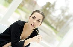 Stirrig raksträcka för kvinna framåt med blyertspennaslutet i mun arkivbilder