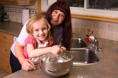 Stirring. Mother teaching her young daughter to stir the pancake dough Stock Photo
