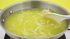 Stirring chicken noodle soup in skillet stock video